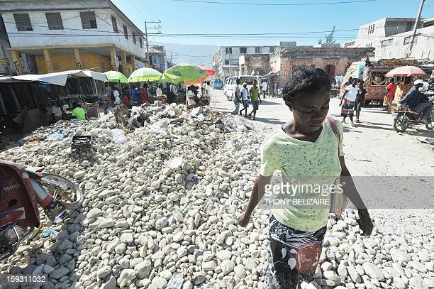 A woman walks through rubble in downtown PortauPrince on January 11 2013 Three years after Haiti was devastated by a massive earthquake hundreds of...