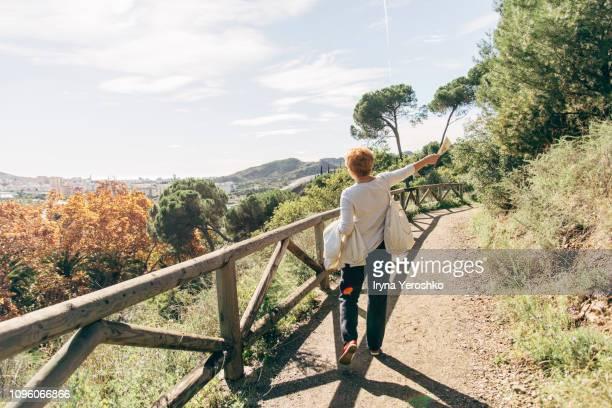 woman walks through scenic park in malaga - malaga fotografías e imágenes de stock