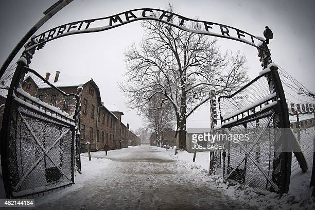 A woman walks through snow near the entrance to the former Nazi concentration camp AuschwitzBirkenau with the lettering 'Arbeit macht frei' in...