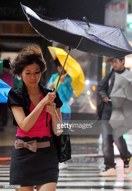 A woman walks through strong winds and rain caused by Typhoon Fitow in Taipei on October 6 2013 Taiwan on October 5 issued a warning over Typhoon...