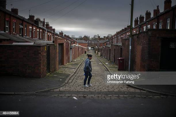 A woman walks through the back alleys of homes in Bolton on February 9 2015 in Bolton United Kingdom As the United Kingdom prepares to vote in the...