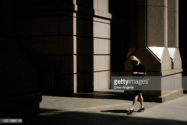 A woman walks through the Financial District August 22 2018 in New York City Today marks the longest bull market rally in US history stretching back...