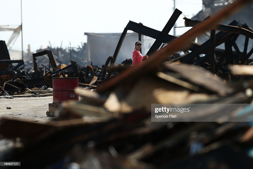 A woman walks through the scene of a massive fire that destroyed dozens of businesses along an iconic Jersey shore boardwalk on September 13, 2013 in Seaside Heights, New Jersey. The 6-alarm fire began in a frozen custard stand on the recently rebuilt boardwalk around 2:30 p.m. and quickly spread in high winds. While there were no injuries reported, many businesses that had only recently re-opened after Hurricane Sandy were destroyed in the blaze.