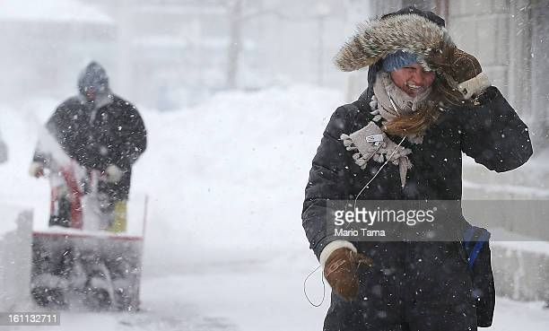 A woman walks through the snow as a worker clears snow from a sidewalk in the Back Bay neighborhood during a lingering blizzard on February 9 2013 in...