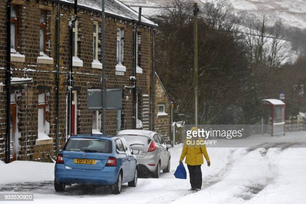 A woman walks through the snow in the village of Marsden east of Manchester in northern England on March 18 as the wintry weather makes a return to...
