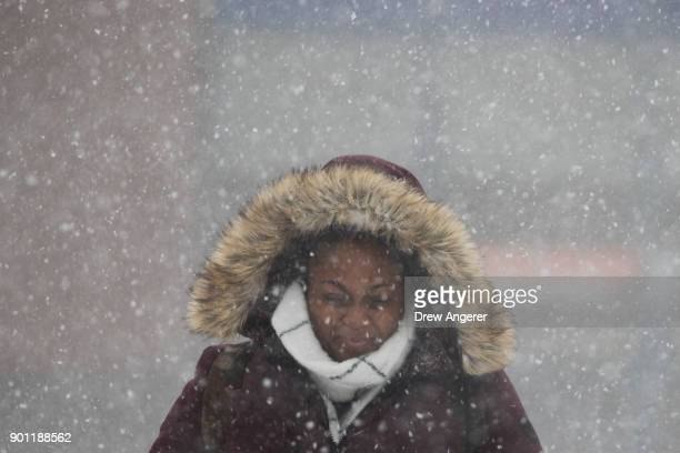 A woman walks through the snow toward the Atlantic AvenueBarclays Center subway station during the morning commute January 4 2018 in the Brooklyn...