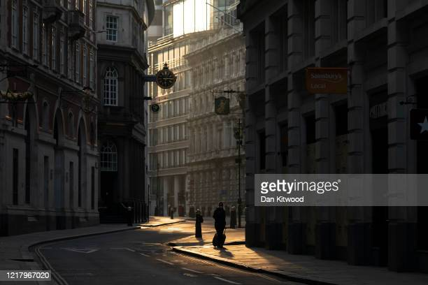 Woman walks through the Square Mile at sunrise on April 10, 2020 in London, England. There have been over 60,000 reported cases of the COVID-19...