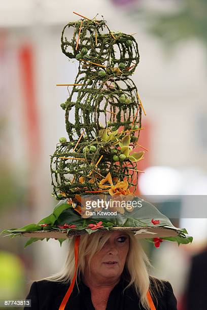 A woman walks through the stands at Chelsea Flower Show wearing a hat created from plants on May 18 2009 in London England The internationally...