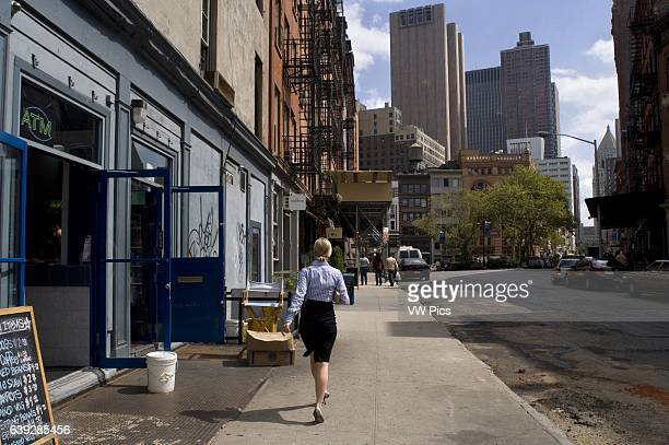 A woman walks through the streets of Soho SoHo and Tribeca are two of the most famous New York known because they are fashionable and because they...