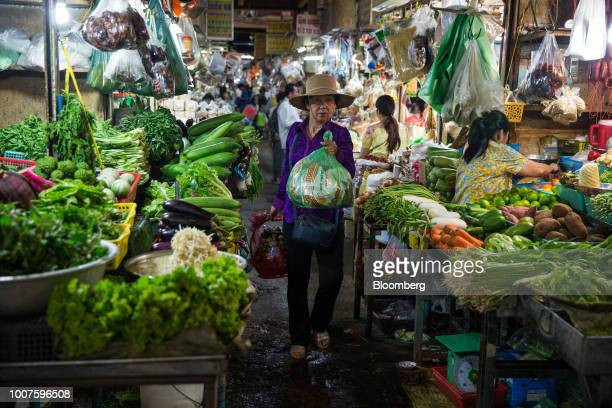 A woman walks through vegetable stalls at Orussey Market in Phnom Penh Cambodia on Friday July 27 2018 Cambodian Prime MinisterHun Senextended his...
