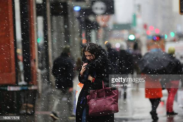 A woman walks through wind snow and sleet on Broadway as Manhattan prepares for a major winter storm on February 8 2013 in New York City New York...