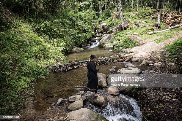 A woman walks to cross a river to reach Patane a place of bodies deceased which located behind a hill during Manene ritual on August 13 2014 in...