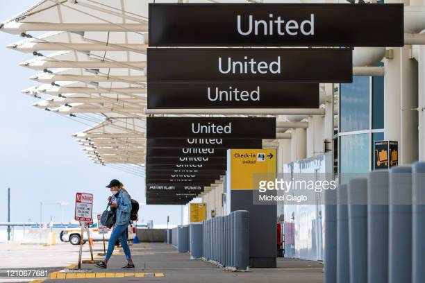 A woman walks to her car at an empty passenger drop off area at Denver International Airport as the coronavirus pandemic slows air travel on April 22...