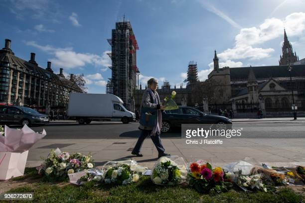 A woman walks to lay a floral tribute in Parliament Square on the first anniversary of the Westminster Bridge terror attack on March 22 2018 in...