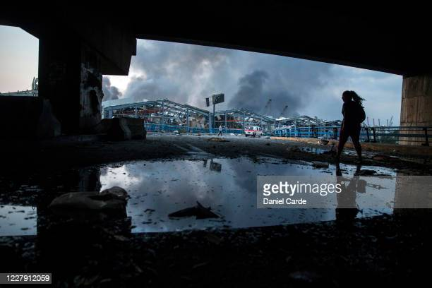 A woman walks toward the port as smoke billows after a large explosion on August 4 2020 in Beirut Lebanon Video shared on social media showed a...