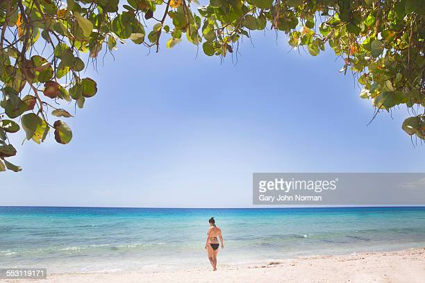 Woman walks towards ocean, La Boca, Cuba