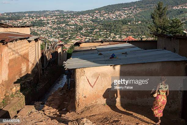 A woman walks towards the entrance of a poor district of Kigali Kigali with a population of more than one million is Rwandas capital and main city...