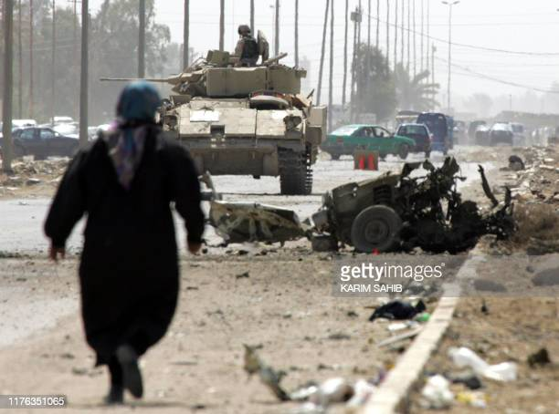 A woman walks towards the site of a car bomb along the highway leading west out of Baghdad towards Abu Ghraib 30 March 2005 The vehicle was parked...