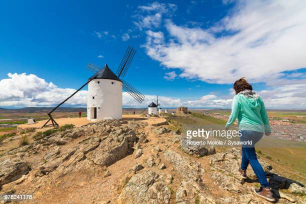 woman walks towards windmills of consuegra, don quixote route, toledo province, castile-la mancha region, spain - トレド ストックフォトと画像