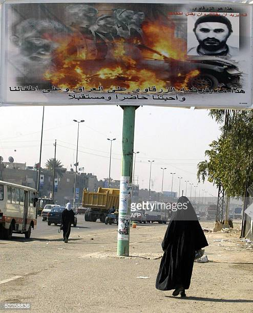 A woman walks under a huge antiterror advertisement showing the image of fire and the portrait of Abu Musab alZarqawi a leading US foe in Iraq on a...