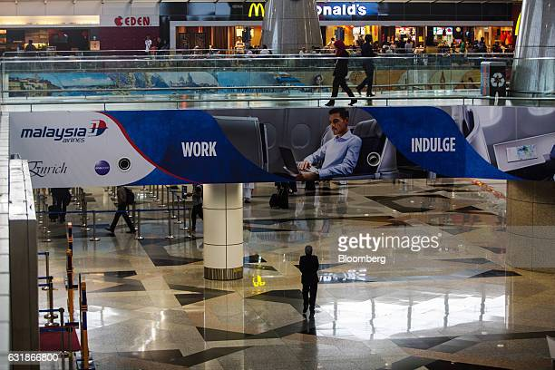 A woman walks under an advertisement for Malaysian Airlines Bhd displayed on the side of a walkway at Kuala Lumpur International Airport in Sepang...
