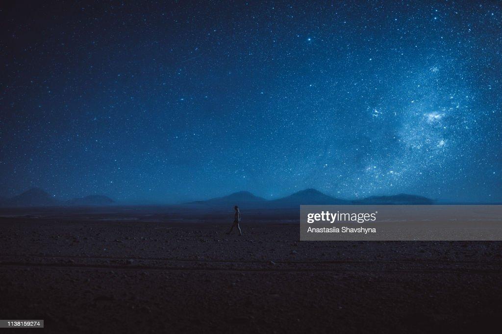 Woman walks under the million stars and Milky Way in Atacama desert : Stock Photo