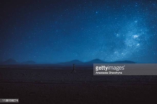 woman walks under the million stars and milky way in atacama desert - night stock pictures, royalty-free photos & images