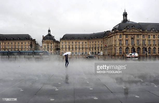 A woman walks under the rain on June 18 2013 in the southwestern French city of Bordeaux The French national weather service issued on June 17 a...