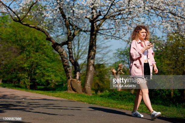 A woman walks under the tree blossom in the holiday sunshine in Alexandra Park in north London on April 10 2020 as warm weather tests the nationwide...