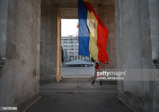 A woman walks under the Triumph Arch next to Moldovan flag on Stefan Cel Mare street in Chisinau city October 8 2013 In Moldova the poorest country...