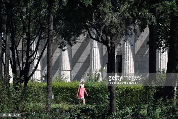 A woman walks under trees past the Temple of Hephaestus at the Ancient Agora in Athens on August 4 2018