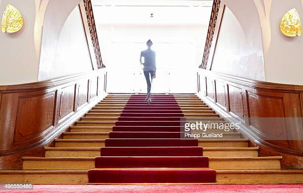 Woman walks up a staircase at Schloss Elmau, a luxury spa hotel, in the Bavarian Alps of southern Germany on June 3, 2014 in Kruen near...
