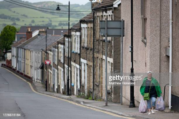 A woman walks up a terraced street carrying two bags of shopping during the coronavirus lockdown period on May 23 2020 in Caerphilly United Kingdom...