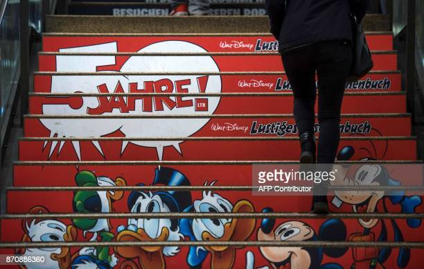 A woman walks up stairs which have been covered with an advert to mark the 50th anniversary of the German version of the Donald Duck pocket books...