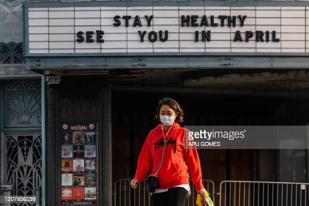 A woman walks wearing a mask to protect herself from the novel coronavirus in front of a closed theater in Koreatown Los Angeles on March 21 2020 All...