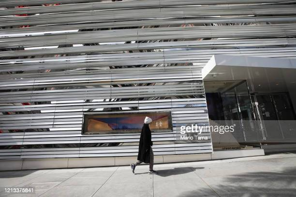 A woman walks while wearing a face mask beneath her chin past a shuttered Louis Vuitton store on iconic Rodeo Drive on March 18 2020 in Beverly Hills...