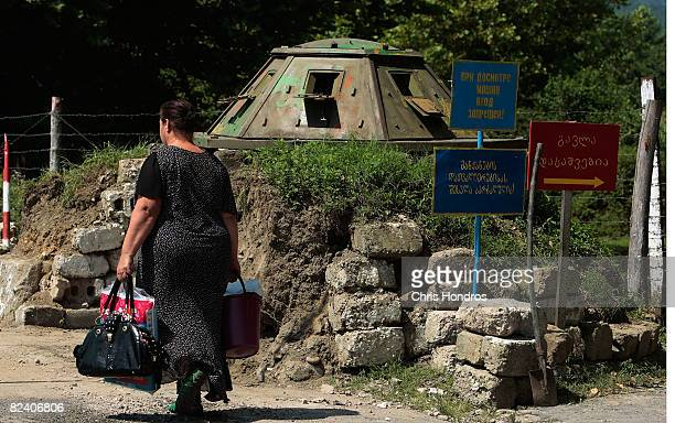 A woman walks with a bag through the border of Georgia and the separatist province of Abkhazia August 18 2008 near Zugdidi Georgia Russian forces...