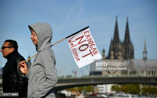 A woman walks with a banner reading Erdogan not Welcome and Cologne's cathedral in the background prior to a demonstration on the theme Erdogan not...