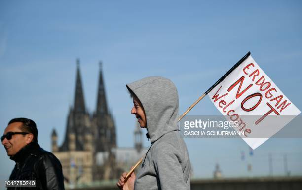 TOPSHOT A woman walks with a banner reading Erdogan not Welcome and Cologne's cathedral in the background prior to a demonstration on the theme...