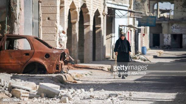 Woman walks with a cane past a destroyed car down a street in Al-Hirak in the eastern Daraa province countryside in southern Syria on June 21, 2018....