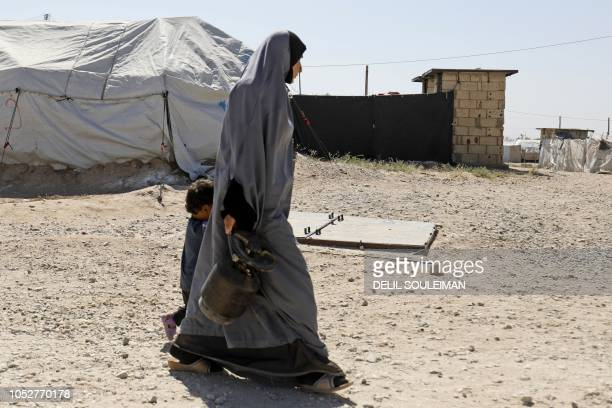 A woman walks with a child at a camp for Islamic State groupaffiliated people in the northern Syrian village of Malikiya near the border with Turkey...