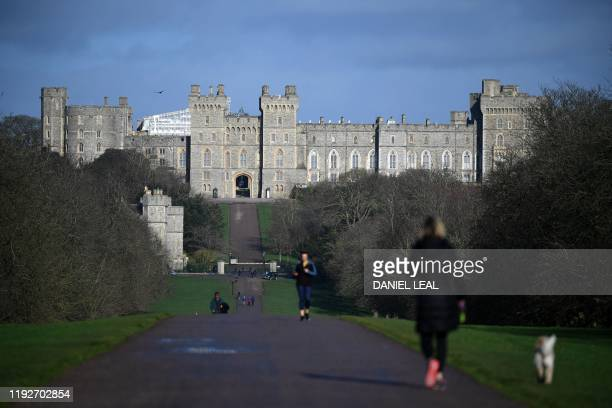 Woman walks with a dog along the Long Walk at Windsor Castle in Windsor, west of London on January 9, 2020. - Britain's Prince Harry and his wife...