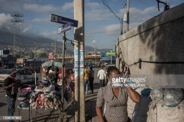 Woman walks with a facemask past a shop in downtown Port-au-Prince on March 26, 2020. - On March 19, President Jovenel Moise announced a halt to all...