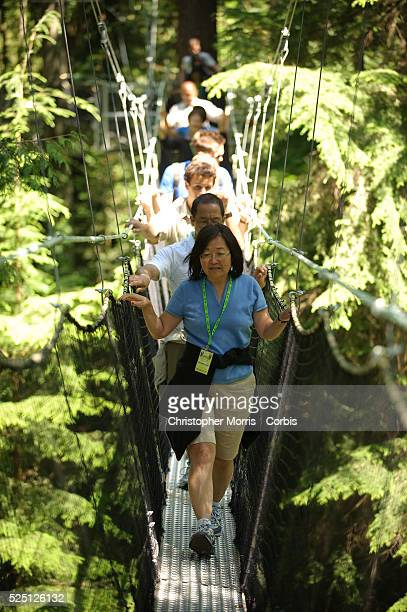 Woman walks with a group across the Greenheart Canopy Walkway at UBC Botanical Garden on the campus of the University of British Columbia. The...
