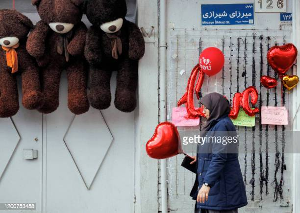 A woman walks with a heartshaped balloon in her hand outside a gift shop displaying Valentine's Day presents and stuffed dolls in the Iranian capital...
