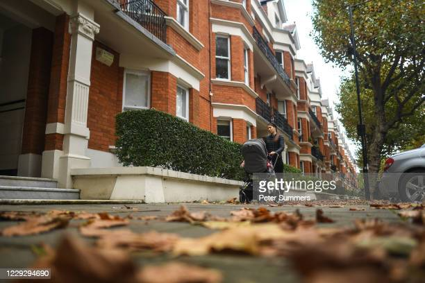 Woman walks with a pushchair past a row of apartments in Maida Vale on October 26, 2020 in London, England. As many young people renting rooms have...