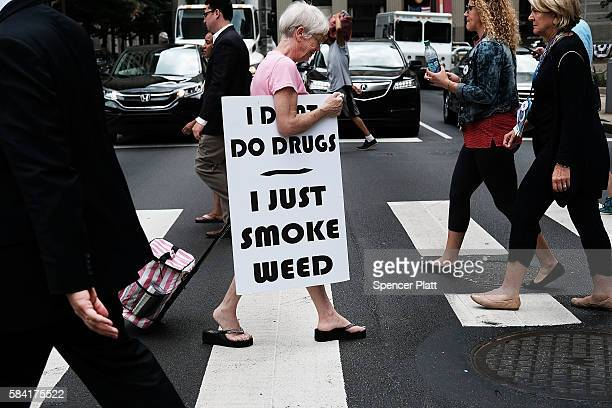 A woman walks with a sign supporting legalizing marijuana during the Democratic National Convention on July 28 2016 in Philadelphia Pennsylvania The...