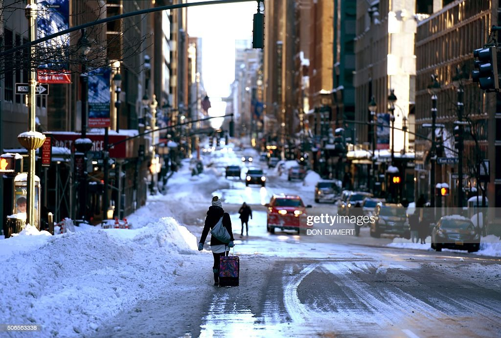 TOPSHOT - A woman walks with a suitcase down a snow-covered street in New York City on January 24, 2016. A massive blizzard that claimed at least 16 lives in the eastern United States finally appeared to be winding down on January 24, giving snowbound residents the chance to begin digging out. / AFP / Don EMMERT