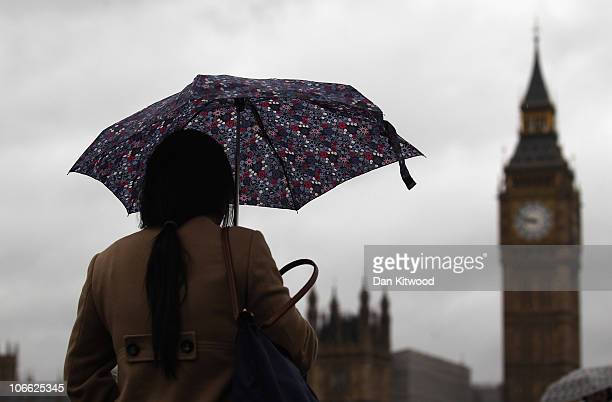 A woman walks with an umbrella across Westminster Bridge on November 8 2010 in London England Forecasters have predicted storms across much of the...