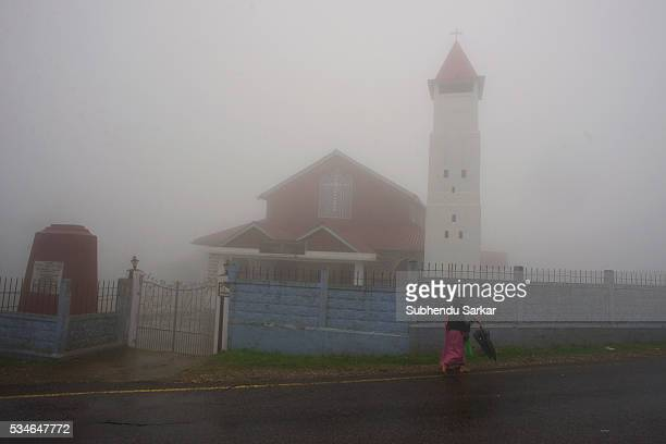 A woman walks with an umbrella along a road in the mist covered Cherapunjee in Meghalaya Cherrapunjee or Charrapunji is a subdivisional town in the...